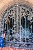 Mujer hispánica que mira a través de la puerta Imagenes de archivo