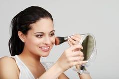 Mujer hispánica que pone en su maquillaje Foto de archivo libre de regalías