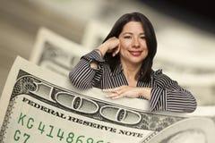 Mujer hispánica que se inclina en cientos billetes de dólar Foto de archivo