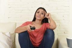 Mujer hispánica que sienta en casa el sofá del sofá en la televisión de observación de la sala de estar que parece cansada y aguj Imagenes de archivo