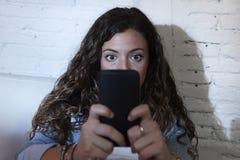 Mujer hispánica que sostiene el teléfono móvil en red de los ojos locos y concepto sociales del apego de Internet Imagenes de archivo
