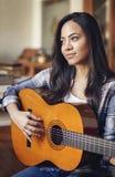 Mujer hispánica que toca la guitarra acústica Imágenes de archivo libres de regalías