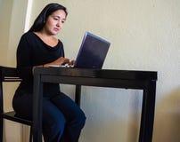Mujer hispánica que trabaja en el ordenador portátil Foto de archivo