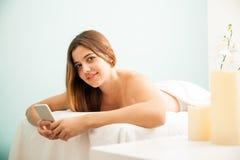 Mujer hispánica que usa smartphone en un balneario Fotos de archivo libres de regalías