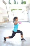 Mujer hispánica del deporte que hace estocadas con la pesa de gimnasia rosada dos, al aire libre Fotografía de archivo