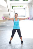Mujer hispánica deportiva en el azul que levanta la pesa de gimnasia rosada que estira ambos brazos hacia fuera para el edificio  Imagenes de archivo
