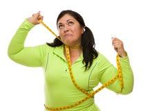 Mujer hispánica enojada implicada con cinta métrica Foto de archivo libre de regalías