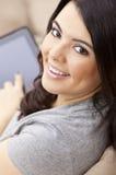 Mujer hispánica feliz que usa el ordenador o el iPad de la tablilla Fotografía de archivo