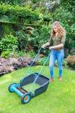 Mujer holandesa joven que empuja el cortacésped en hierba Imágenes de archivo libres de regalías