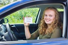 Mujer holandesa joven que muestra el carné de conducir de la tarjeta en coche Fotos de archivo