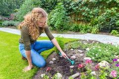 Mujer holandesa joven que rastrilla en jardín Fotografía de archivo libre de regalías