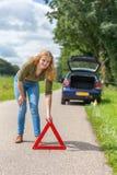 Mujer holandesa que pone el triángulo amonestador del peligro en el camino rural Fotos de archivo