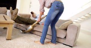 Mujer hoovering la alfombra mientras que el socio relaja la TV de observación Imagenes de archivo