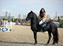 Mujer a horcajadas en un caballo Foto de archivo libre de regalías