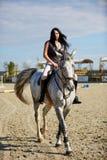 Mujer a horcajadas en un caballo Imagen de archivo libre de regalías
