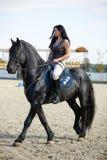 Mujer a horcajadas en un caballo Fotos de archivo