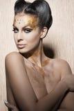 Mujer imponente con maquillaje de oro de lujo imagen de archivo