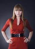 Mujer imponente en alineada roja en fondo negro Imagen de archivo