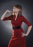 Mujer imponente en alineada roja en fondo negro Foto de archivo libre de regalías