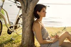Mujer inactiva en el amor que espera debajo de un árbol de aceituna imagenes de archivo