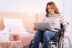 Mujer incapacitada sonriente que trabaja en su ordenador portátil imagenes de archivo