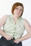 Mujer incapaz de abotonar vaqueros Foto de archivo libre de regalías