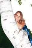 Mujer, inclinándose contra el tronco del abedul Imagen de archivo libre de regalías