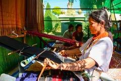 Mujer indígena que demuestra la tela que teje foto de archivo libre de regalías