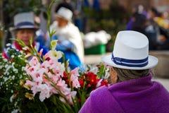 Mujer indígena que vende las flores en la plaza de Imagenes de archivo