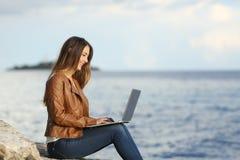 Mujer independiente que trabaja con un ordenador portátil en la playa Imagen de archivo