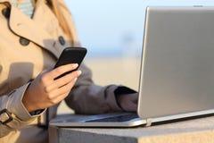 Mujer independiente que trabaja con un ordenador portátil y un teléfono Fotografía de archivo