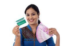 Mujer india alegre que lleva a cabo un manojo de rupia india y de crédito Imagen de archivo