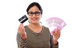 Mujer india alegre que sostiene tarjetas de la rupia india y de crédito Fotos de archivo