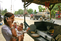 Mujer india con el bebé que habla en su teléfono móvil en un lugar del restaurante del borde de la carretera Imagen de archivo libre de regalías