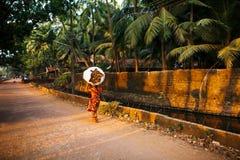 Mujer india con un bolso grande y pesado de la maleza en su cabeza en una sari roja Va a lo largo del canal de río con las palmer fotografía de archivo libre de regalías
