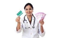 Mujer india del doctor que lleva a cabo 2000 notas de la rupia y que hace el pulgar para arriba Imagenes de archivo