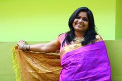 Mujer india en la situación y la sonrisa púrpuras de la sari Imagenes de archivo