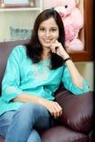 Mujer india feliz joven que se sienta en el sofá Imagen de archivo libre de regalías