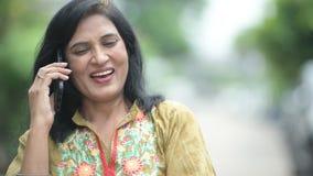 Mujer india hermosa feliz madura que habla en el teléfono mientras que piensa en las calles al aire libre almacen de video