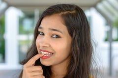 Mujer india joven pensativa que muerde su finger Foto de archivo libre de regalías