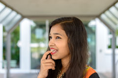 Mujer india joven pensativa que muerde su finger Imagen de archivo