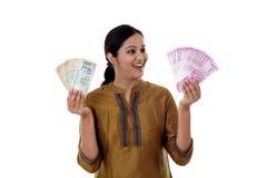 Mujer india joven que lleva a cabo 2000 y 100 notas de la moneda Fotos de archivo libres de regalías