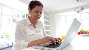 Mujer india mayor que usa el ordenador portátil en casa almacen de metraje de vídeo