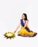 Mujer india que hace rangoli usando las flores Foto de archivo