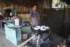 Mujer india que prepara el dosa en una cocina, Auroville Imagen de archivo