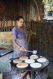 Mujer india que prepara el dosa en una cocina, Auroville Imagen de archivo libre de regalías