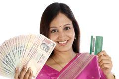 Mujer india que sostiene la tarjeta india de la moneda y de crédito Foto de archivo