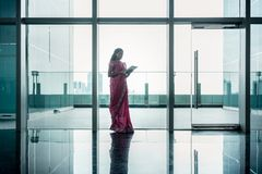 Mujer india que usa la tableta en el pasillo del buildi corporativo moderno imagen de archivo libre de regalías