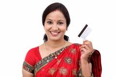 Mujer india tradicional alegre que sostiene una tarjeta de crédito Foto de archivo libre de regalías