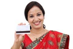 Mujer india tradicional alegre que sostiene una tarjeta de crédito Foto de archivo